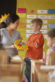 Female teacher helping student tell time — Stock Photo