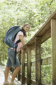 Woman leaning against a forest railing — Stock Photo