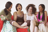 Group of women on sofa laughing — Stock Photo