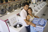Couple hugging in laundromat — Stock Photo