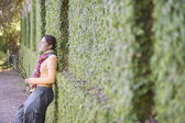 Woman leaning against a hedge — Stock Photo
