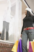 African American woman with bags window shopping — ストック写真