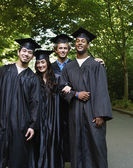 Four college graduates standing together — Foto de Stock