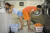 Couple bent over washer and dryer in laundromat — Photo