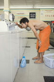 Man wrapped in towel lifting washer lid in laundromat — Stock Photo