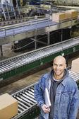 Man standing in front of conveyor belt — Stock Photo