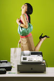 Asian woman with shopping bag kicking up heel next to cash register — Stock Photo