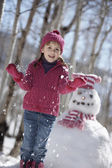 Portrait of girl with snowman — Stock Photo