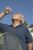 Senior Asian man with tennis racket drinking water — Stock Photo