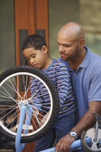 Father helping son fix bike — Stock Photo