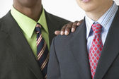 African American businessman's hand on businessman's shoulder — Stock Photo