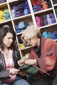 Woman knitting in front of yarn — Stockfoto
