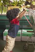 Young African American boy pushing shopping cart — Stock Photo