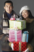 Young couple with holiday gifts — Stock Photo