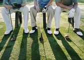 Golfers sitting on bench — Stock Photo