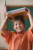 Young boy holding books on his head — Stock Photo