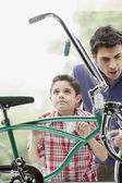 Boy with father looking at bike through store window — Stock Photo