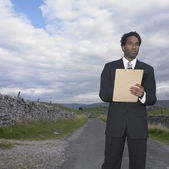 Businessman writing on a clipboard in rural location — Stock Photo