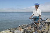 Woman with bike looking out over lake — Stock Photo