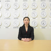 Businesswoman with time zone clocks on the wall behind her — Stock Photo