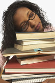 Young woman sleeping on a pile of books — Stok fotoğraf