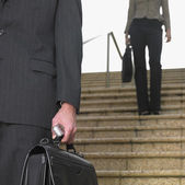 Businessman and businesswoman descending stairs — Stock Photo