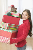 Portrait of teenager holding stack of gifts in front of Christmas tree — Stock Photo