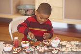 Young boy making gingerbread men — Stock Photo