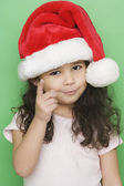 Portrait of girl wearing Santa hat and pointing — Stock Photo