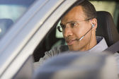 Man with earpiece in car — Stock Photo
