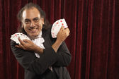 Portrait of magician with cards fanned in hand — Stock Photo