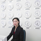 Businesswoman working with time zone clocks on the wall behind her — Stock Photo