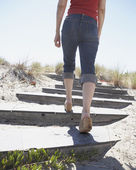 Rear view of lower section of woman walking up stairs at beach — ストック写真