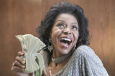 Close up of African American woman holding stack of 100 dollar bills — Stok fotoğraf