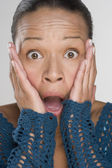 Portrait of surprised woman with hands on face — Stock Photo