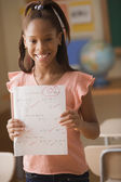 Young girl showing off test score of 100 — Foto de Stock
