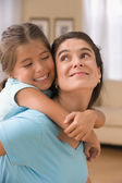 Mother giving daughter piggy back ride — Stock Photo