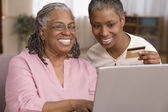 Mother and daughter ordering online with credit card — Stock Photo