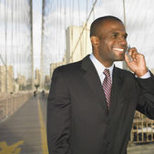 Businessman on bridge talking on cell phone — Stock Photo