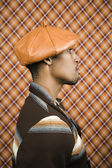Profile view of young man wearing a leather hat — Stock Photo