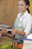 Woman handing credit card to cashier in store — Stock Photo