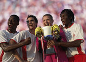 Soccer team triumphantly holding trophy — Stock Photo