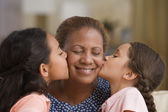 Daughters kissing each of their mother's cheeks — Stock Photo