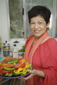 Middle aged woman holding a plate of peppers — Stock Photo