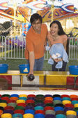 Couple playing with a fairground attraction — Stock Photo
