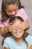 Girl with hands over another girl's face — Stock Photo