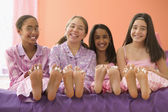 Four girls sitting on bed with bare feet — Stock Photo
