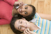 Portrait of two girls laying on floor talking on cell phones — Stock Photo