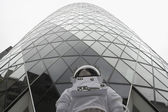 Low angle view of an astronaut standing by a skyscraper — Stock Photo
