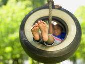 Portrait of girl on tire swing — Stock fotografie